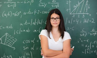 Intelligent young female maths student or teacher wearing glasses standing in front of a chalkboard with mathematical equations with folded arms and a piece of chalk in her hand