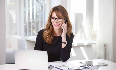 Portrait of executive financial woman sitting at desk and working on laptop while making call.