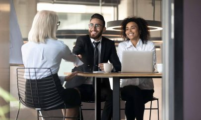 Multi-ethnic business partners greet each other shake hands sit at desk in modern office room, Arabian HR manager handshake welcoming applicant elderly female rear view starting job interview concept